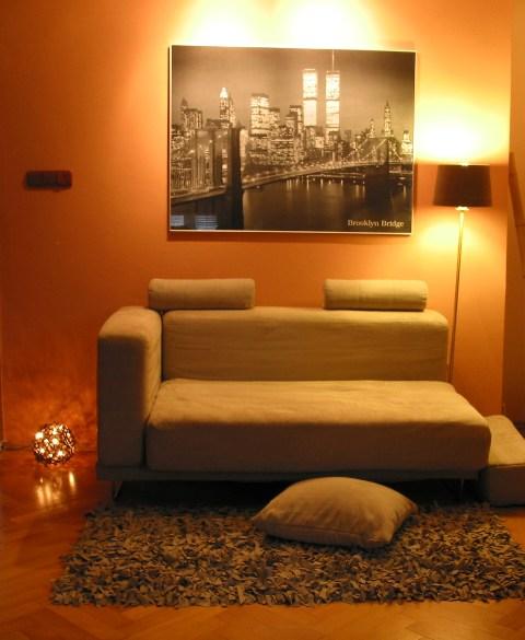 moderna siva sedacka v obyvacke s drevenymi parketami a oranzovou malovkou, obrazom New Yorku a svetelnou gulou